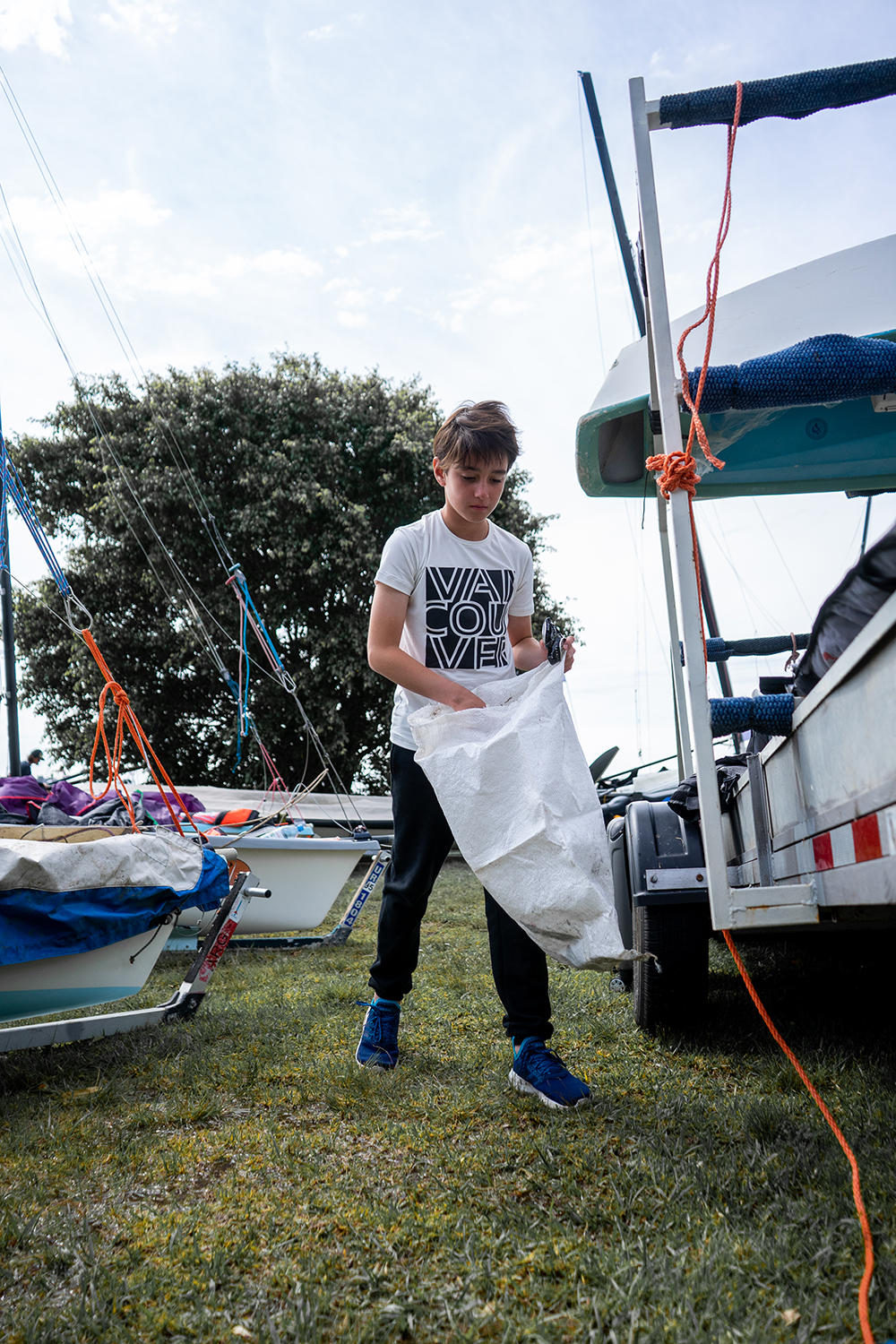 Sailors clean up debris around their sailing center. Photo credit: Unplastify