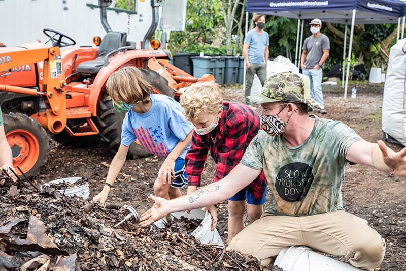 Showing the kids how temperature is monitored in the compost pile. Credit: Rafael Bergstrom | Sustainable Coastlines Hawaii 2021