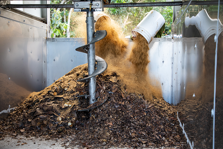 """Adding carbon-rich """"brown"""" material to the compost pile inside the self-contained vessel. Credit: Rafael Bergstrom 